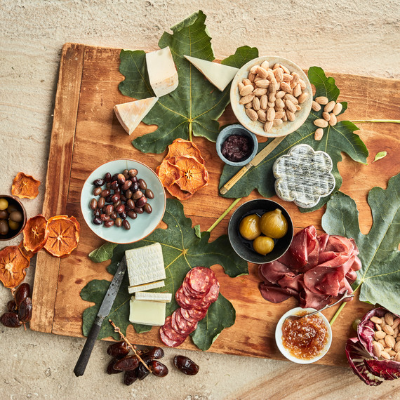 serving board with almonds and meats olives