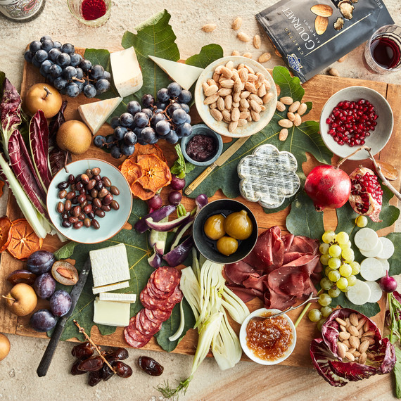 serving board with almonds and meats olives pomegranate