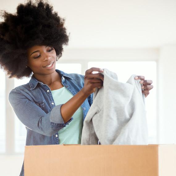 woman packing sweater in cardboard box