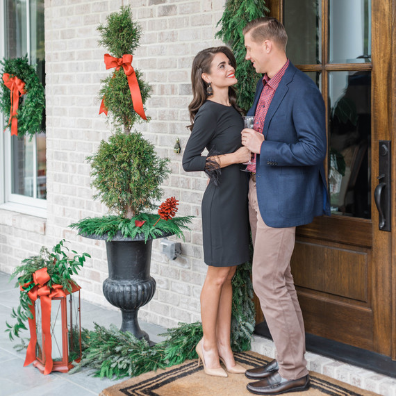 couple standing at christmas doorfront