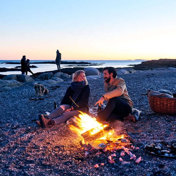couple sitting on beach with bon fire