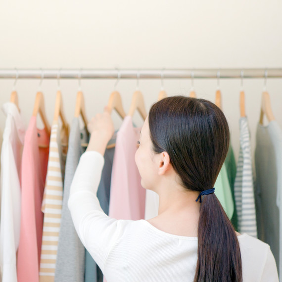 woman with ponytail looking through clothing rack