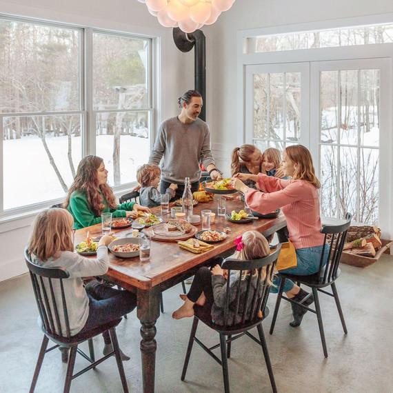 family eating dinner at vintage farm table near wood-burning stove