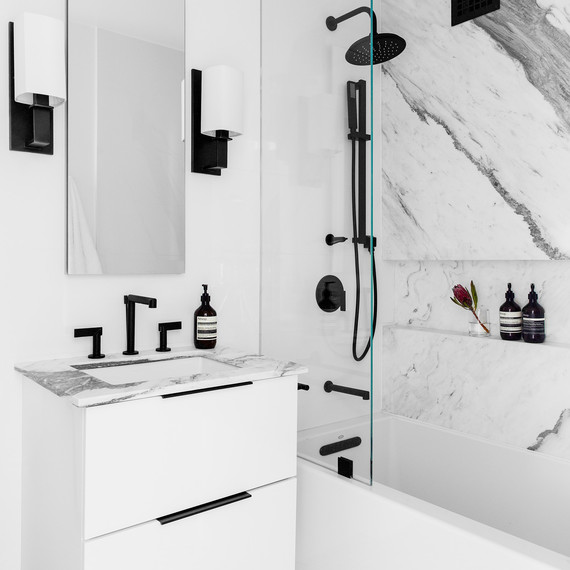 bathroom with marble sink and shower and black accents