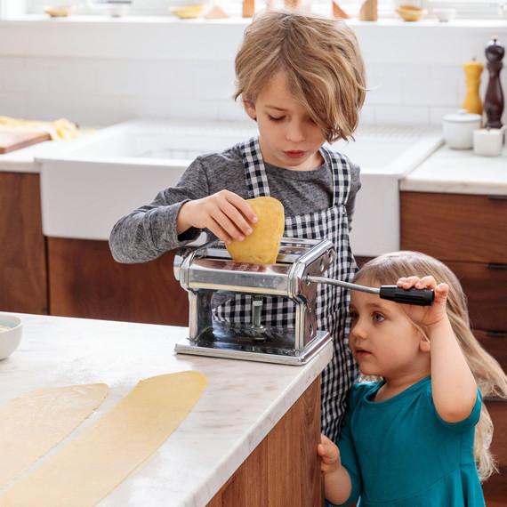 boy and girl hand-cranking pasta