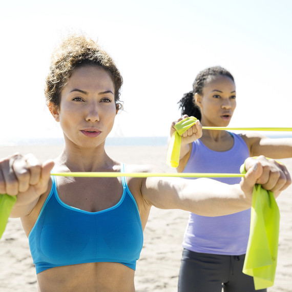 women using resistance bands on the beach