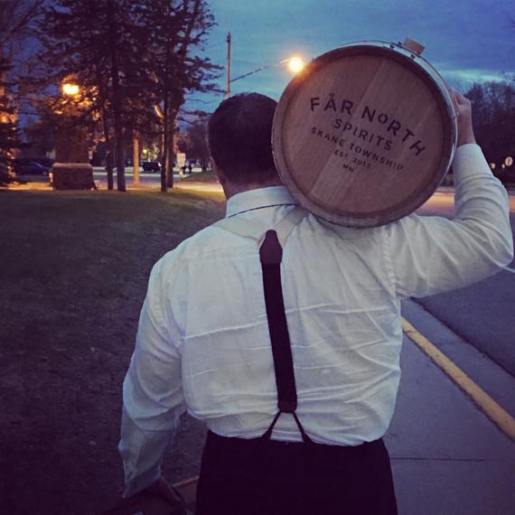 man carrying far north distillery barrel