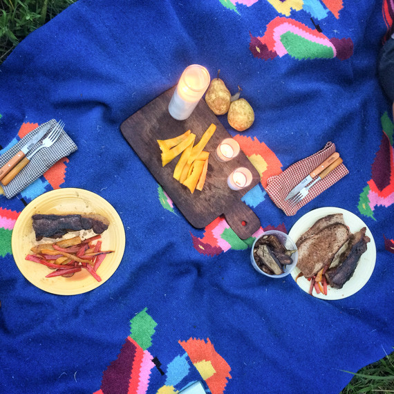 blue blanket used for picnic with peppers and grilled meat