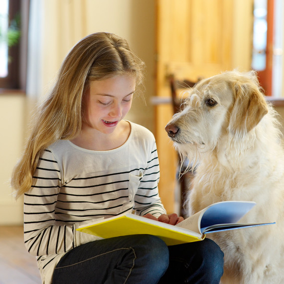 girl in kitchen reading book to large dog