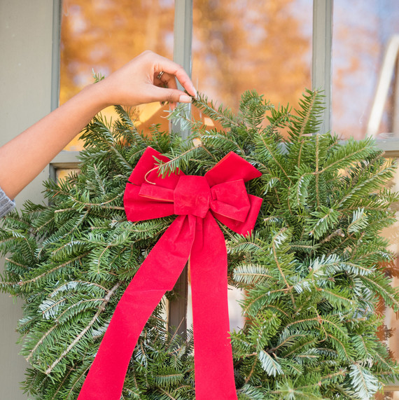 wreath with red ribbon getting hung on door