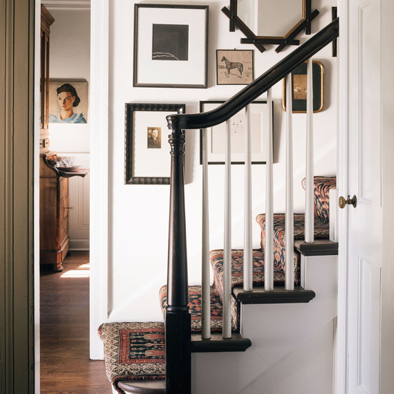 staircase with stair runner and vintage art