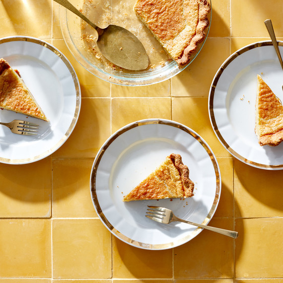 slices of buttermilk cardmom pie on gold and white plates