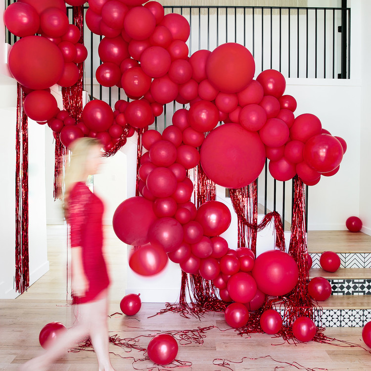 haunted movie house red balloon installation on staircase with blurry movoing woman