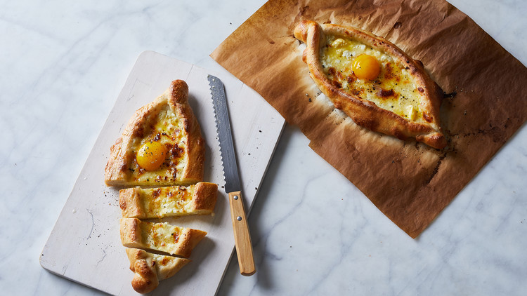 khachapuri sitting on white cutting board with knife