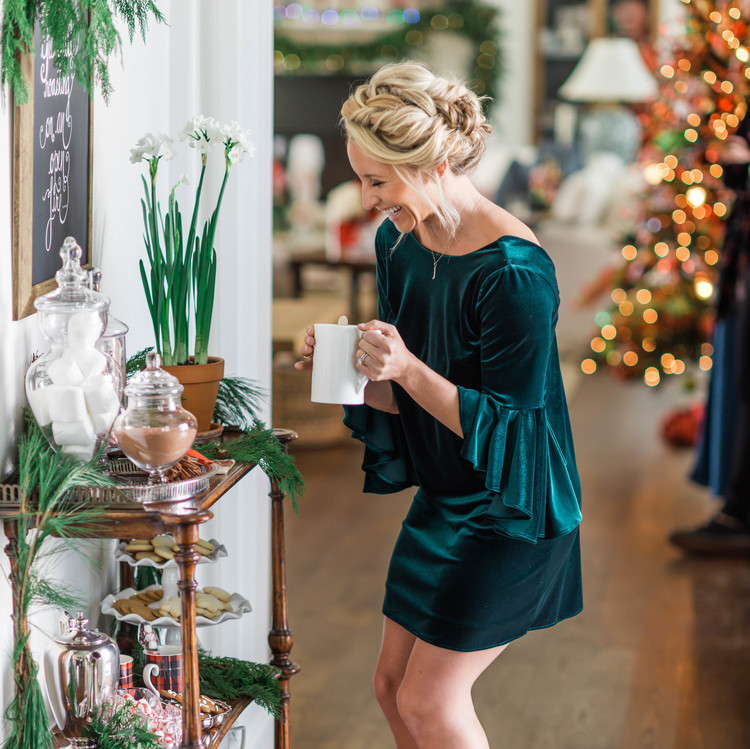 woman in green dress standing next to drink bar cart