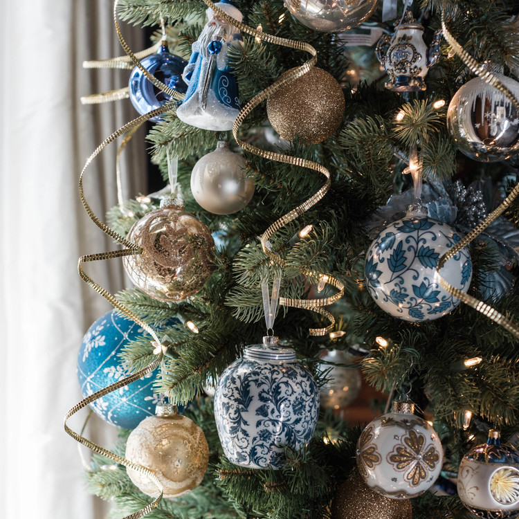 christmas tree with gold and blue ornaments and spiral ribbon
