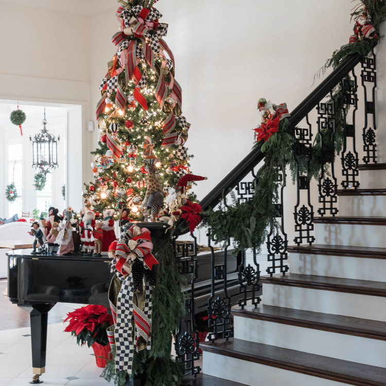 staircase with garland next to piano and christmas tree