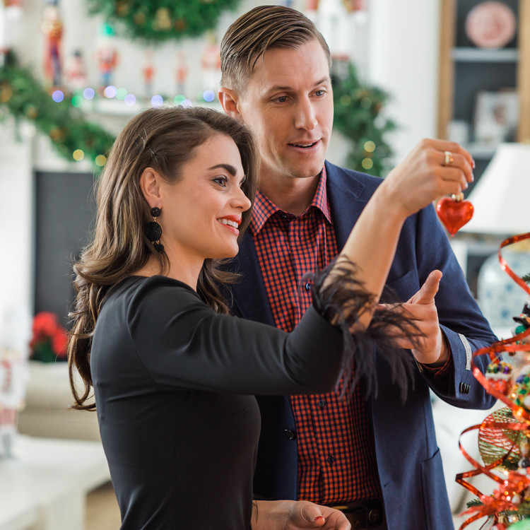couple hanging ornament on tree