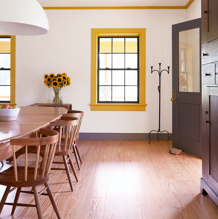 dining room with long wooden table and yellow accents