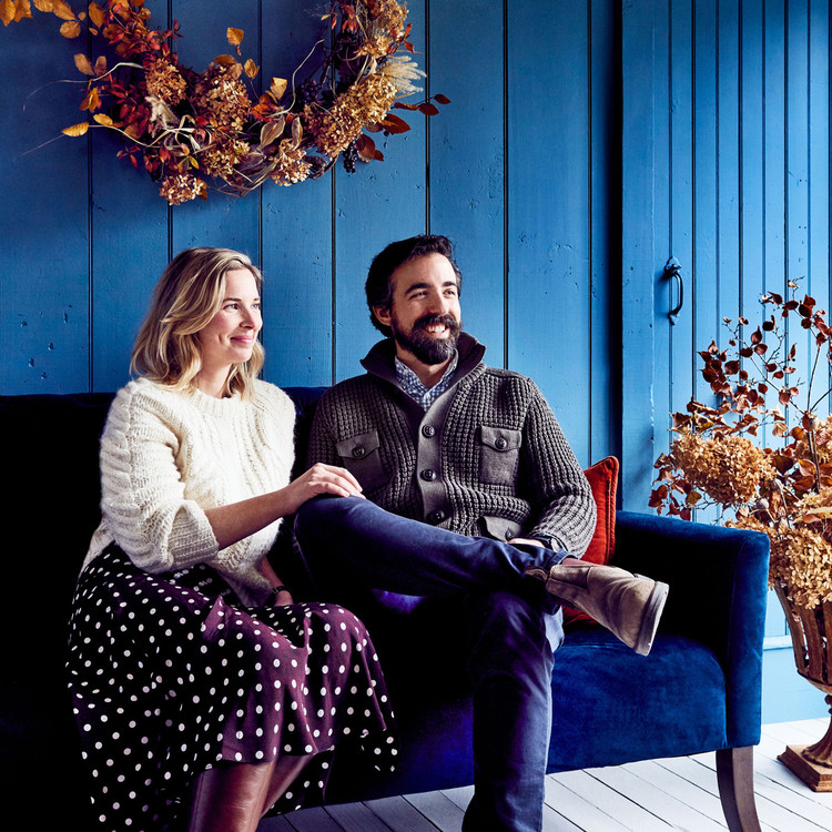 couple sitting on blue couch beneath wreath
