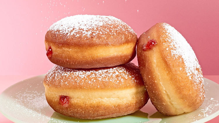 strawberry jam-filled doughnut getting sprinkled with powdered sugar