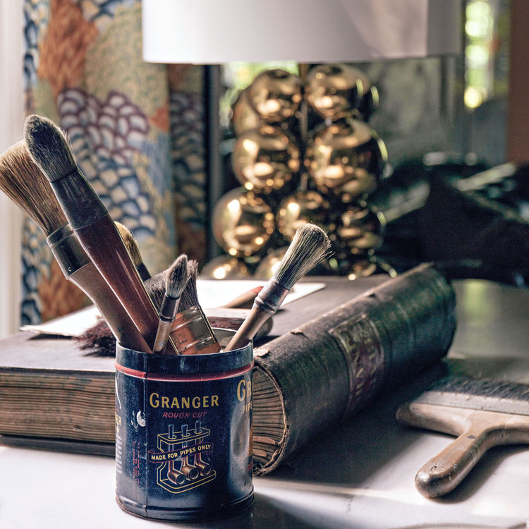 antique book and vintage can filled with paintbrushes