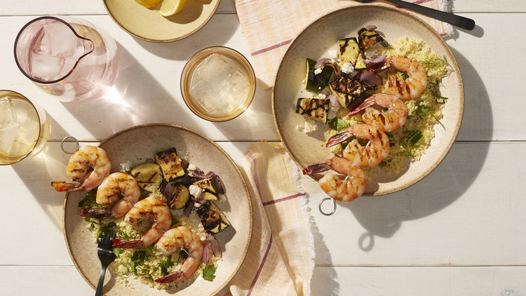 greek shrimp skewers with chopped zucchini salad at place settings